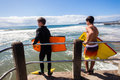 Surfing bodyboarders waves pier jump boys ready to into ocean off to surf morning ocean at surf city durban south africa Royalty Free Stock Image