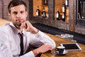 Surfing the net in bar handsome young man shirt and tie holding hand on chin and smiling while sitting at counter with digital Stock Photo