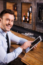Surfing the net in bar handsome young man shirt and tie working on digital tablet and smiling while sitting at counter Royalty Free Stock Photo