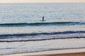 Surfing rider sup unidentified ocean early morning with one surfer unrecognizable paddling on the having a fun work out and Royalty Free Stock Images