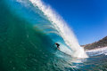 Surfing wave tube ride action rider inside a large hollow swimming water photo image of the surfer Stock Images