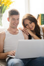 Surfing web together beautiful young couple sitting close to ea each other and reading books Royalty Free Stock Photography