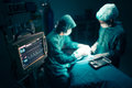 Surgeons team working with monitoring of patient in surgical operating room selective focus on monitor Royalty Free Stock Photos