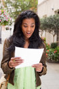 Surprise african american woman reading document looking surprised Stock Image