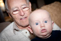 Surprise baby in the foreground with his grandfather in the background baby has a surprised look on his face Royalty Free Stock Photo