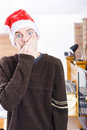 Surprise christmas man gasping standing indoor in a home interior wearing hat covering mouth in shock xmas Stock Photos