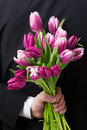 Surprise flowers close up of man holding a bunch of behind his back Royalty Free Stock Photo