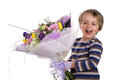 Surprise gift of flowers smiling boy with a bouquet as a for birthday mothers day or valentine s day Stock Image