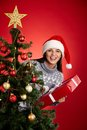 Surprise out of firtree portrait happy girl in santa cap holding red giftbox and looking at camera decorated Royalty Free Stock Image