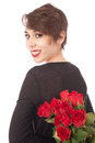Surprise with a rose yong woman holds at her back and is smiling gently Royalty Free Stock Photo