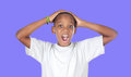 Surprised african adolescent on a blue background Royalty Free Stock Photography
