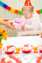 Surprised baby receiving present on first birthday Royalty Free Stock Images