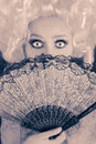 Surprised baroque woman monochrome portrait with wig and fan style of a beautiful behind a hand Royalty Free Stock Photo