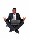 Surprised black man a businessman sitting on the floor with a laptop on his lap and is very what he sees on his computer over Stock Photography