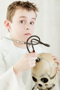 Surprised boy checking skull with stethoscope Royalty Free Stock Photo