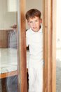 Surprised boy peeks from behind door indoor Royalty Free Stock Photos