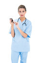 Surprised brown haired nurse in blue scrubs using a mobile phone on white background Stock Photos