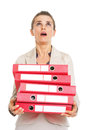 Surprised business woman with stack of folders looking up on copy space Royalty Free Stock Photos