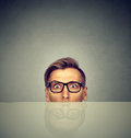 Surprised businessman peeking from under table Royalty Free Stock Photo