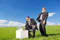 Surprised businessmen conceptual shot of with laptop in green meadow Stock Photography