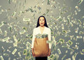 Surprised businesswoman holding money young paper bag with under dollar s rain Royalty Free Stock Photos