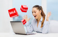 Surprised businesswoman with laptop and sale signs Royalty Free Stock Photo