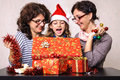 Surprised child looking in christmas present box extremely little girl at her mother and aunt adult women with boxes and Stock Photos