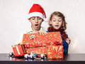 Surprised children looking in christmas present box shocked boy and girl expression Stock Photos