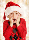 Surprised christmas boy years old in santa hat portrait on lights background Royalty Free Stock Photo