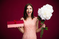 Surprised cute woman holding gift box and flowers