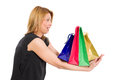Surprised or excited woman holding shopping bags heavy on her arms isolated on white background Royalty Free Stock Images