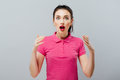 Surprised funny teenage girl showing empty copy space with her finger grey background. Happy girl pointing, looking at
