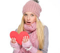 Surprised girl reading heart shaped postcard in winter clothes Stock Images