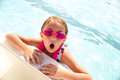 Surprised girl typing on laptop in swimming pool Royalty Free Stock Photo