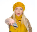 Surprised girl using tv remote control in autumn clothes Stock Image