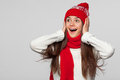 Surprised happy beautiful woman looking sideways in excitement. Christmas girl wearing knitted warm hat and scarf, isolated on gra Royalty Free Stock Photo