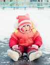 Surprised kid sitting on the ice in winter Stock Photos