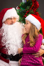 Surprised little girl looking at fake santa claus with fake bear pulling beard down while sitting on lap Stock Photo
