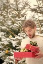 Surprised man holding two red boxes in snow wood Royalty Free Stock Photo