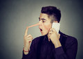 Surprised man with long nose talking on mobile phone Liar concept Royalty Free Stock Photo