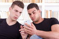 Surprised man showing phone message to his friend men two friends with one white in living room atmosphere Stock Photography