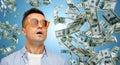 Surprised man under dollar money rain