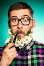 Surprised man young in glasses and a beard of flowers smoking a pipe Royalty Free Stock Photos