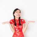 Surprised oriental woman in red qipao portrait of surprise young asian traditional dress with hand opened and looking up Stock Image