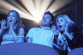 Surprised people watching horror movie in theatre young screaming while the Stock Photography
