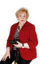 Surprised picture taking grandmother a very looking senior woman sitting in a red jacket holding a camera in her hand isolated for Royalty Free Stock Image