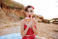 Surprised pin up girl showing two cream cakes sitting outdoors Royalty Free Stock Photo