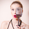 Surprised pinup woman looking through spatula beautiful blond Royalty Free Stock Photos