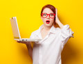 Surprised redhead girl in white shirt with computer Royalty Free Stock Photo