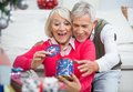 Surprised senior woman with man looking at women men christmas gift home Stock Photos